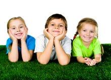 Garçon et filles se trouvant sur une herbe verte Photo stock