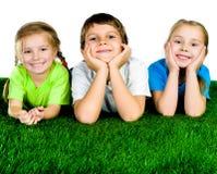 Garçon et filles se trouvant sur une herbe verte Photos libres de droits