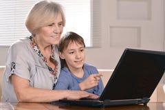 Garçon et grand-mère avec l'ordinateur portable Photos stock