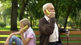 Garçon et grand-père employant la banane comme téléphones, jouant le jeu drôle ensemble, plaisanterie banque de vidéos