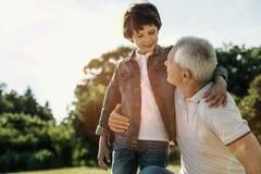Garçon et grand-papa étreignant et regardant l'un l'autre Photographie stock