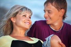 Garçon et jeune femme sur la plage, regardant contre Photographie stock libre de droits