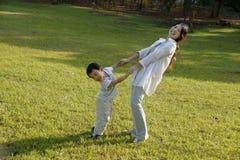 Garçon et mère ayant l'amusement sur la pelouse Images stock
