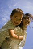 Garçon et mère ayant l'amusement sur la pelouse Image libre de droits