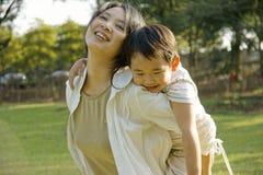 Garçon et mère ayant l'amusement sur la pelouse Images libres de droits