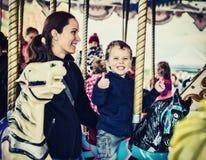 Garçon et mère heureux sur le carrousel - rétro photos stock