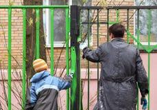 Garçon et père, ils teignent la frontière de sécurité par couleur verte Photos libres de droits
