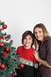 Garçon et sa maman souriant près de l'arbre de Noël Image stock