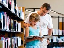 Garçon et son père dans la bibliothèque Photographie stock