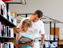 Garçon et son père dans la bibliothèque Image libre de droits