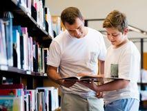 Garçon et son père dans la bibliothèque Photos libres de droits