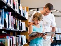 Garçon et son père dans la bibliothèque Photo libre de droits