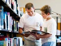 Garçon et son père dans la bibliothèque Images stock