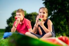 Garçon et une fille mangeant la pastèque un jour ensoleillé Photographie stock