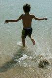 Garçon exécutant dans l'eau Image stock