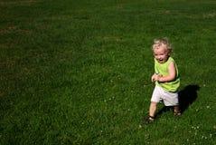 Garçon exécutant sur l'herbe en stationnement Photographie stock