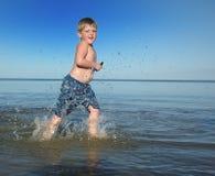 Garçon exécutant sur la plage Photos stock