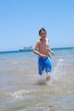 Garçon exécutant sur la plage Images libres de droits
