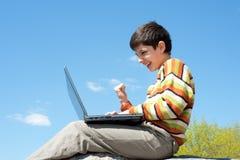 Garçon Excited jouant avec l'ordinateur portatif sans fil Images stock