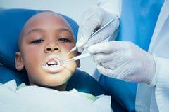 Garçon faisant examiner ses dents par le dentiste images stock