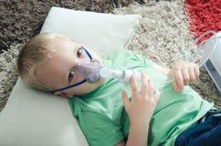 Garçon faisant l'inhalation avec le nébuliseur à la maison Images stock