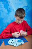 Garçon faisant le flocon de neige de papier rose avec des ciseaux Photographie stock libre de droits