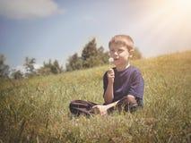 Garçon faisant le pissenlit souhaiter sur une colline verte Image libre de droits