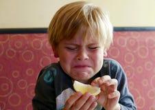 Garçon faisant un visage drôle après avoir mordu un citron photographie stock libre de droits
