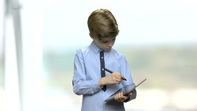 Garçon faisant une note sur le comprimé numérique banque de vidéos