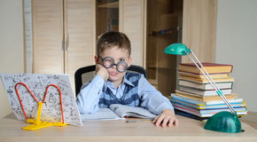 Garçon fatigué en verres drôles faisant le travail Enfant avec des difficultés d'apprentissage Garçon ayant des problèmes avec so Photo stock