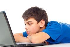 Garçon fatigué pour le jeu d'ordinateur portable Images stock