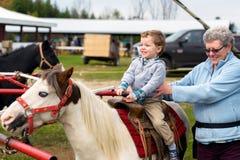 Garçon fier sur sa première Pony Ride Images libres de droits