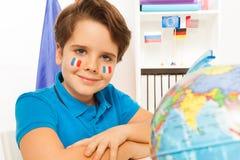 Garçon français mignon apprenant la géographie avec le globe Photo stock