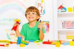 Garçon futé en verres avec des outils de travail de jouet Photo stock