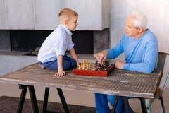 Garçon futé mignon s'asseyant sur la table Photographie stock libre de droits