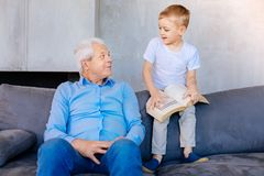 Garçon futé mignon tenant un livre Photo libre de droits