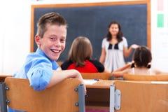 Garçon gai dans la chambre de classe Photographie stock libre de droits