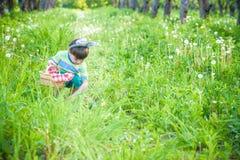 Garçon gai jugeant le panier plein des oeufs de pâques colorés se tenant sur l'herbe en parc après chasse à oeufs Photo stock