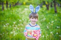 Garçon gai jugeant le panier plein des oeufs de pâques colorés se tenant sur l'herbe en parc après chasse à oeufs Image libre de droits