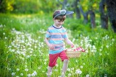 Garçon gai jugeant le panier plein des oeufs de pâques colorés se tenant sur l'herbe en parc après chasse à oeufs Photographie stock