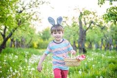 Garçon gai jugeant le panier plein des oeufs de pâques colorés se tenant sur l'herbe en parc après chasse à oeufs Photos libres de droits