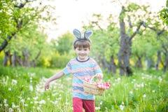 Garçon gai jugeant le panier plein des oeufs de pâques colorés se tenant sur l'herbe en parc après chasse à oeufs Image stock