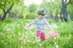 Garçon gai jugeant le panier plein des oeufs de pâques colorés se tenant sur l'herbe en parc après chasse à oeufs Photos stock
