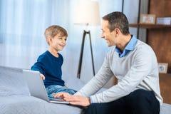 Garçon gai parlant avec son père sur le lit Image stock