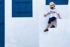 Garçon gai sur le fond du bâtiment Blanc-bleu Le concept grec photo stock