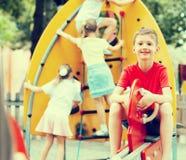 Garçon gai sur le terrain de jeu des enfants Photo libre de droits