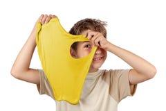 Garçon gai tenant une boue jaune et regardant par son trou image stock