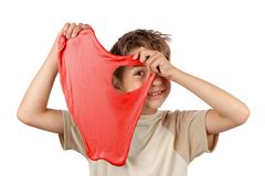 Garçon gai tenant une boue rouge et regardant le jet son trou image stock
