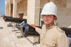 Garçon habillé comme dans le vieil uniforme militaire anglais devant les canons à La Valette, Malte Photos stock