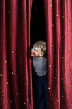Garçon habillé vers le haut de en tant que rideau en Peeking Thru Stage de clown photos stock